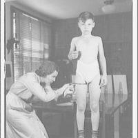 Dr. Eleanor Hunt. Dr. Hunt measuring width of boy's thigh