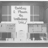 """Electric Institute of Washington. Window display of electric ranges with sign, """"Cooking's a pleasure the Westinghouse way"""""""