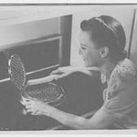Electric Institute of Washington. Woman cleaning waffle iron