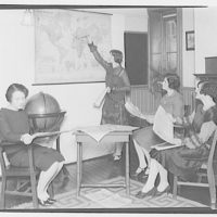 Fairmount School, 1711 Massachusetts Ave. Women studying newspapers and map at Fairmount School