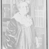 Folger Library interiors. Mrs. Folger standing by fireplace in reading room
