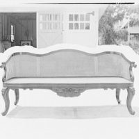 Furniture and other home furnishings. Chaise lounge with cane backing in front of garage, with masking