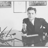 Gas company advertising photographs. Man seated at desk pointing pencil