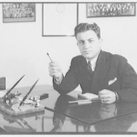 Gas company advertising photographs. Man seated at desk pointing pencil I