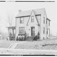 Miscellaneous houses. Two-story stucco house with wood trim and porch on left side