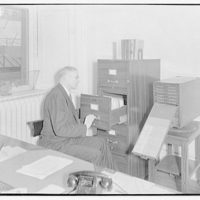 Miscellaneous subjects. Man seated at filing cabinet