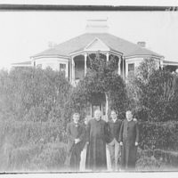 Portrait photographs. Four men, two in clerical dress, standing in front of a house