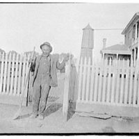 Portrait photographs. Man with shovel leaning on gate
