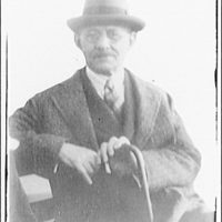 Portrait photographs. Portrait of a seated man wearing a hat and holding a cane copied for Cohen's Inc.