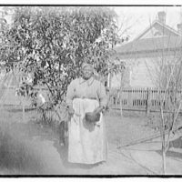 Portrait photographs. Woman wearing kerchief holding pan and spoon in front of house