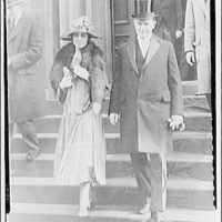 Portrait photographs. Woman with hat and fur stole and man with tophat going down stairs