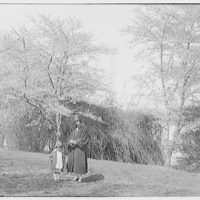 Theodor Horydczak and family. Fritzie and Norma Horydczak standing on grass with trees in background IV