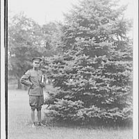 Theodor Horydczak and family. Theodor Horydczak in uniform standing next to conifer