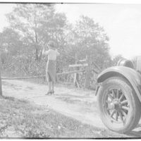 West Virginia trip. Woman at gate on dirt road with car in background