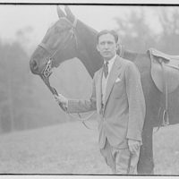 American Legion Horse Show in Wheaton, Maryland. Man standing by a horse and holding it by its bridle I