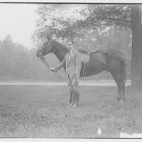 American Legion Horse Show in Wheaton, Maryland. Man standing by a horse and holding it by its bridle II
