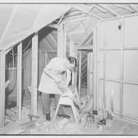 Mr. and Mrs. A.W. Koch, residence at 42 Hawthorne St., Lynbrook, Long Island. Attic, with Mr. Koch at work
