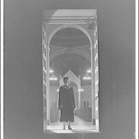 Trinity College. Student in graduation gown standing in doorway Trinity College campus